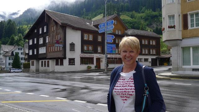 Frau vor Strassenkreuzung im Dorf.