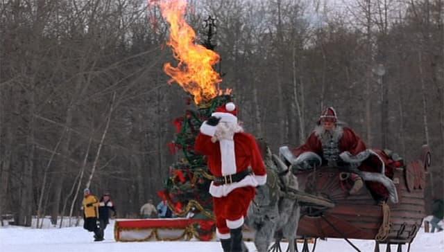Weihnachtsmann mit Schlitten hinter einem anderen Nikolaus.