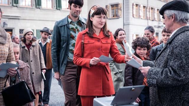 Eine Frau im roten Anzug hält Stimmzettel in der Hand, die sie gerade einem Mann im grauen Anzug abgibt.