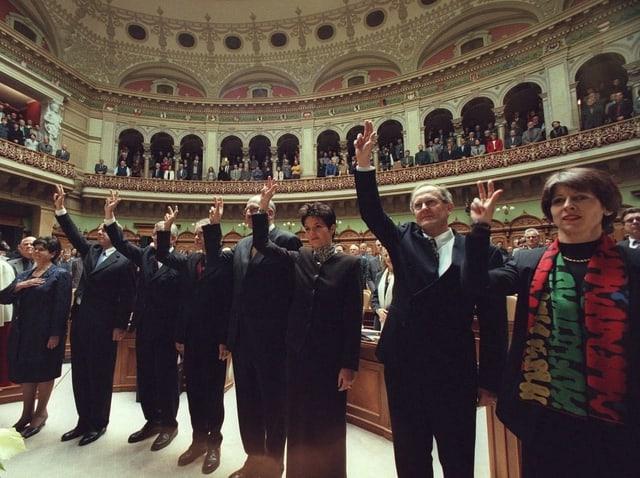 Im Nationalratssaal. Bundesratsmitglieder und Huber-Hotz, sekundiert von Weibel, erheben die Hand zum Schwur.