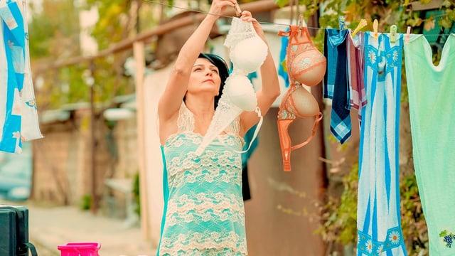 Frau hängt Wäsche auf.