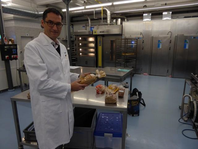 Ein Mann in weissem Kittel in einem Labor.