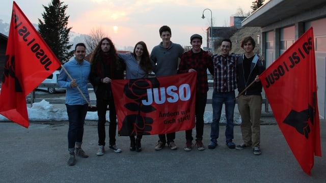 6 giuvens ed ina giuvna stattan en ritscha cun bandieras cotschnas da la partida Juso