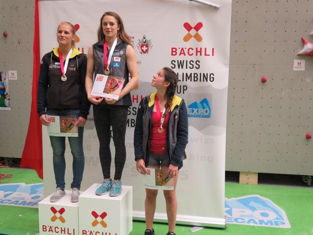 Drei junge Frauen auf einem Siegerpodest