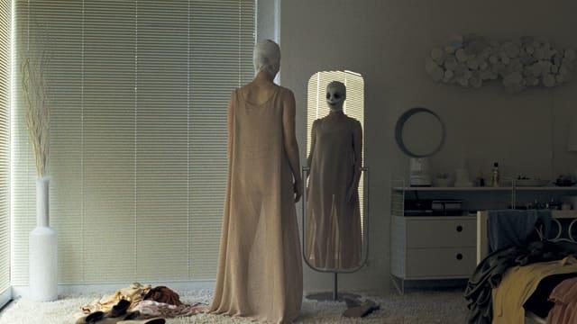 Eine Frau mit einbandagiertem Kopf steht im Halbdunkel vor einem Spiegel