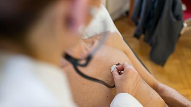 Ein Arzt horcht einen Patienten mit einem Stethoskop ab.