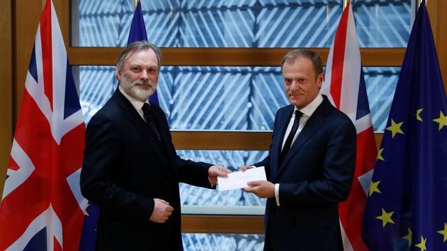 Der britische EU-Botschafter Tim Barrow (l.) übergibt Donald Tusk das Austrittsschreiben. Daneben stehen EU- und Grossbritannien-Fahnen.