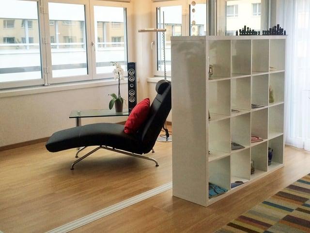 Ein moderner Sessel steht im Wohnbereich auf hellem Parkett, davor ein weisses, quadratisches Büchergestell.