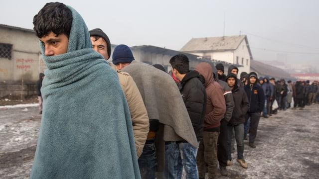In Decken eingehüllte junge Männer stehen in der Kälte Schlange und warten auf die Essensausgabe
