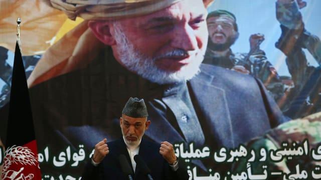 Präsident Hamid Karzai bei seiner Rede zur Übernahme der Sicherheitsverantwortung in Afghanistan. Im Hintergrund ein grosses Bild eines solzen afghanischen Mannes mit Turban.