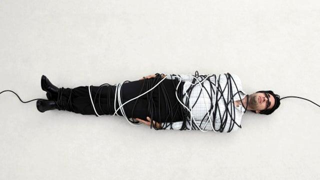 Ein Mann in schwarzer Hose und weissem Hemd liegt auf dem Boden, gefesselt von weissen und schwarzen Kabeln.