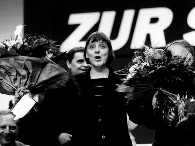 Angela Merkel mit einem Blumenstrauss in jeder Hand.