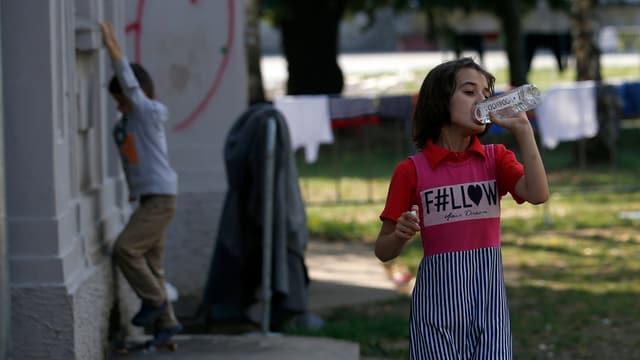 Ein Mädchen trinkt Wasser.
