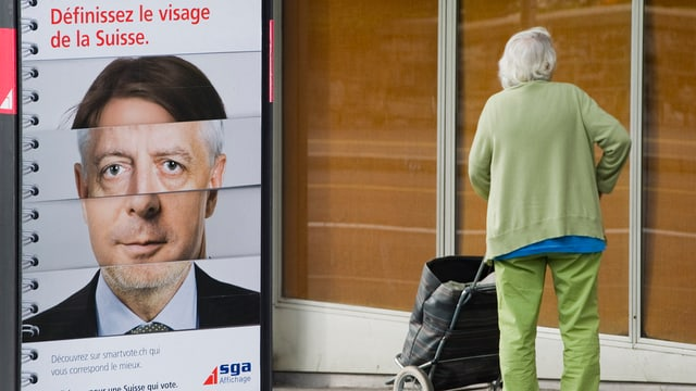 Eine alte Frau steht vor einem Plakat von smartvote.