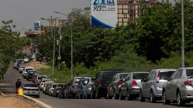 Eine lange Autokolonne wartet am Strassenrand, um Benzin aufzufüllen.