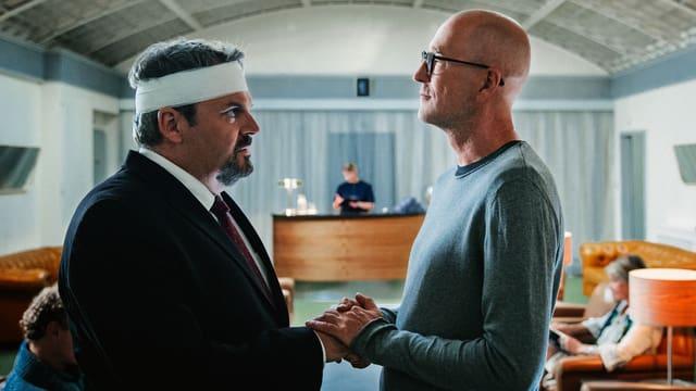 Professor Mankovsky hält die Hand von Luc Conrad. Er ist am Kopf verletzt und trägt einen Verband um den Kopf.