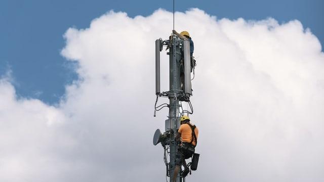 Menschen montieren eine Mobilfunk-Antenne