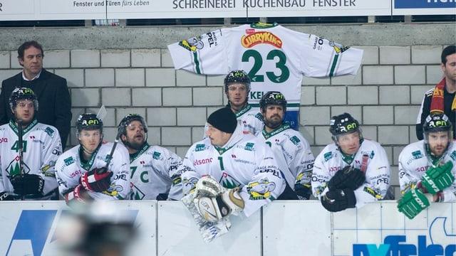Eishockeyspieler hinter der Bande, dahinter an der Wand das Trikot mit der Nummer 23.