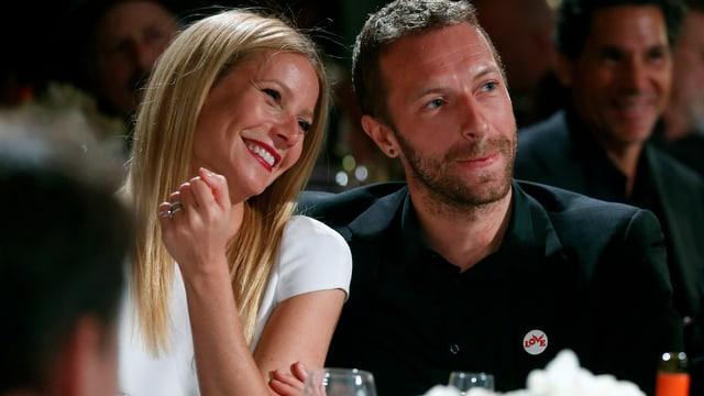 Gwyneth Paltrow und Chris Martin sitzen verliebt nebeneinander. Er trägt einen schwarzen Anzug, sie ein weisses Kleid.