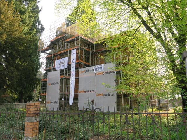 Besetztes eingerüstetes Haus mit Transparenten.