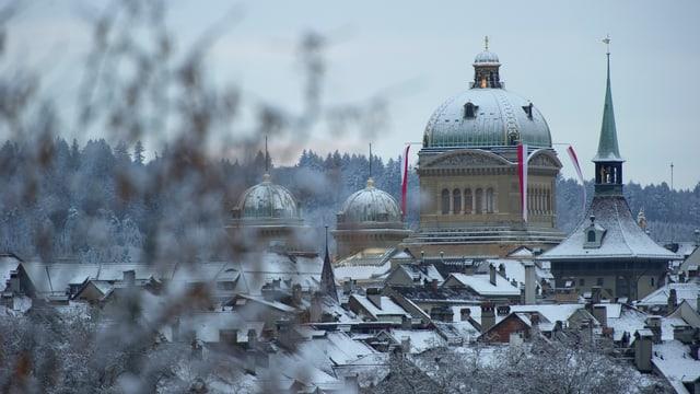 Symbolbild: Die Bundeshauskuppel aus der Ferne, eine dünne Schneedecke ziert die Dächer.