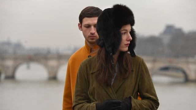 Ein Mann und eine Frau stehen auf einer Brücke in Paris.