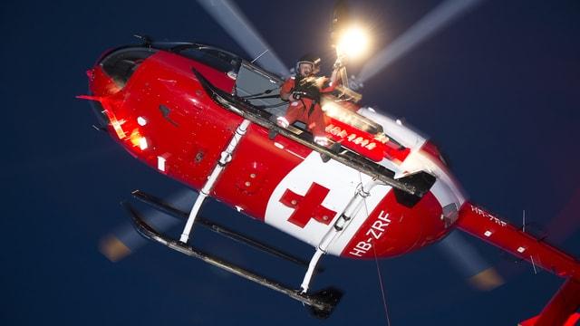 Ein Helikopter der Rega fliegt vor dem Nachthimmel