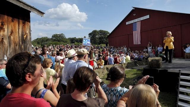 Hillary Clinton steht auf einer Bühne neben einer Farm