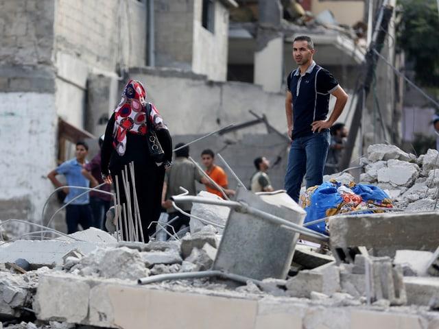 Eine Familie steht in Trümmern.
