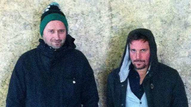 Zwei junge Männer stehen von einer Wand.