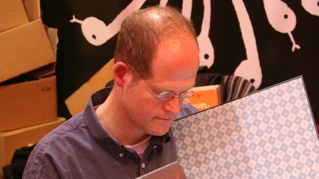 Nahaufnahme des Comic-Autors Chris Ware, während er in einem Buch blättert.
