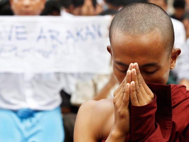 Ein buddhistischer Mönch steht mit gefalteten Händen und gesenktem Blick vor einem Protestplakat.