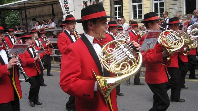 Musicants en giaccas cotschnas e cun chapella, che sunan durant marschar atras ina via da la citad da Cuira.