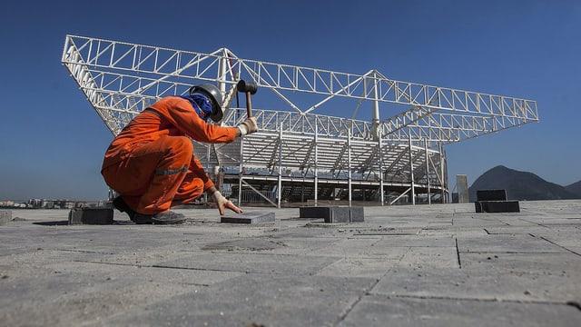 Ein Bauarbeiter hämmert Steinplatten ein.
