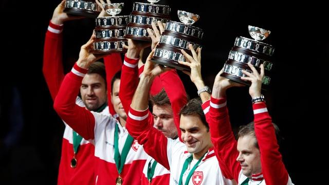 Die Schweizer Tennis-Spieler stemmen ein ihren persönliche Pokale über die Köpfe.