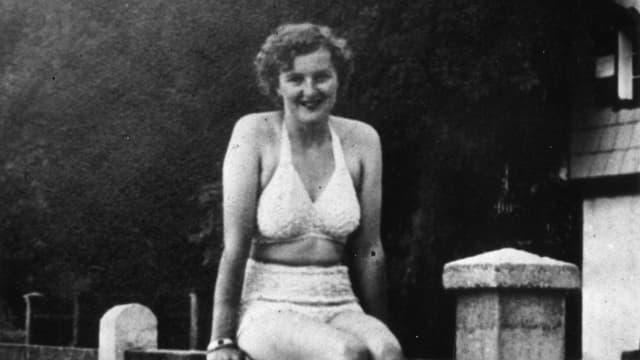 Junge Frau sitzt auf einem Zaun, altes Foto.
