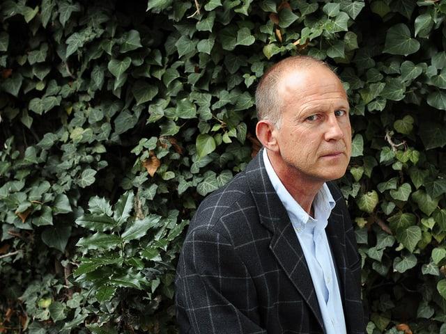 Der britische Schriftsteller Tim Parks vor einer Efeuwand.