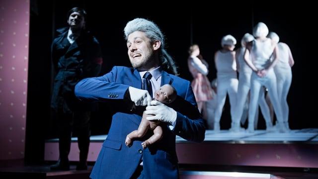Ein Mann auf einer Bühne mit einer Puppe im Arm, der er den Arm auszureissen droht.