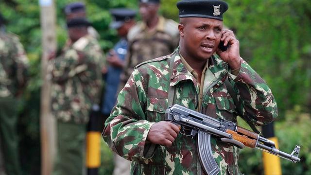 Bewaffneter enianischer Soldat mit einem Mobiltelefon.