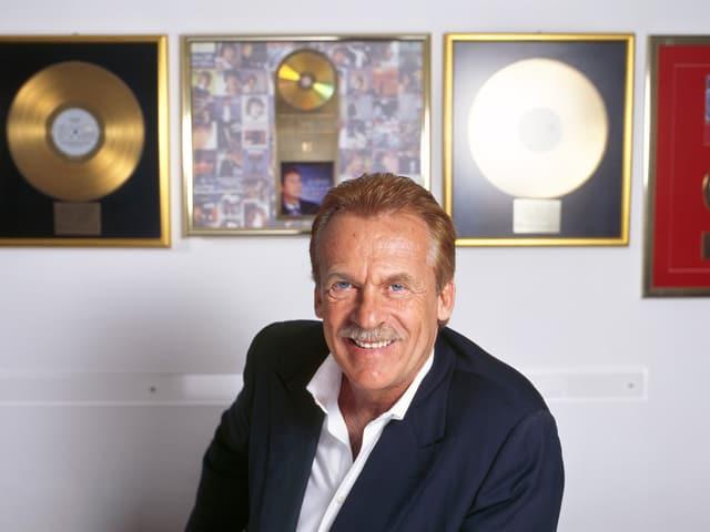 Ein Mann im weissen Hemd und dunklen Jackett sitzt vor einer Wand, an der goldene Schallplatten hängen.