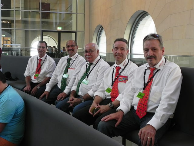 Fünf Männer mit weissem Hemd und Krawatte sitzen in einer Reihe.