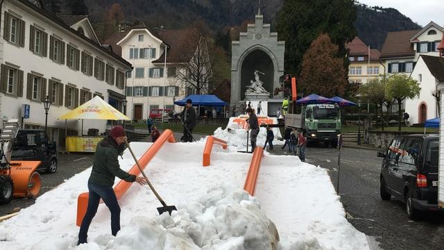 Junge Leute verteilen Schnee und platzieren Hindernisse.