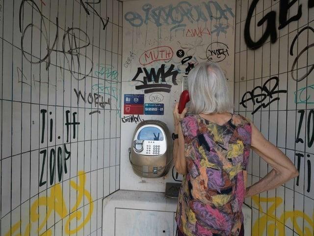 Eine Frau telefoniert in einer Telefonkabine.