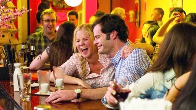 Eine Frau und ein Mann sitzen lachend am Tresen einer japanischen Bar.