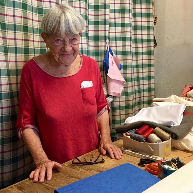 Maria Krebs hinter dem Ladentisch auf dem ein Meter, ihre Brille, stoffe und Fadenspulen liegen.