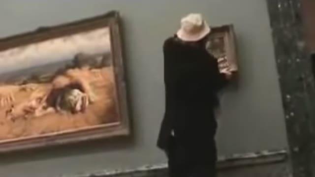 Ein Mann mit Hut hängt ein Bild im Museum auf.