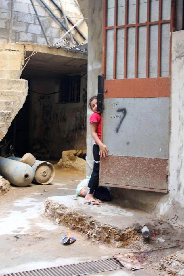 Mädchen versteckt sich hinter einer Tür