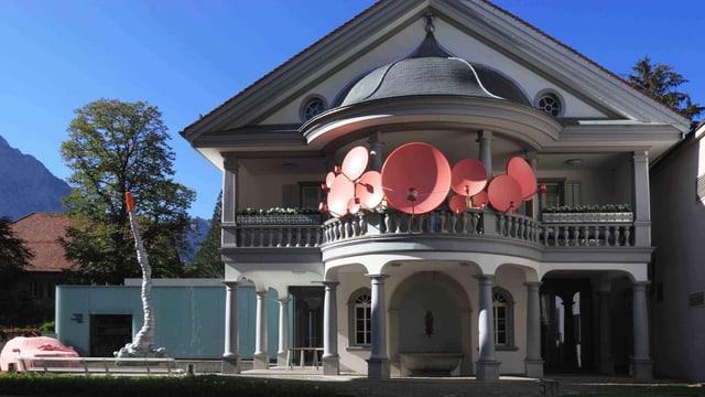 Das Haus für Kunst in Uri mit rosafarbenen Satellitenschüsseln auf dem Balkon.