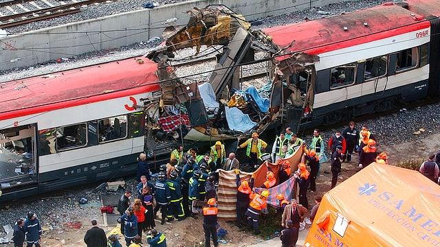 Zerstörter Zug, Rettungskräfte im Vordergrund