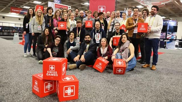 19 verschiedene Schweizer Gamestudios, im Vordergrund drei rote Würfel mit einem gamifizierten Schweizerkreuzlogo.